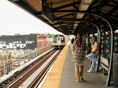 A J train enters an above-ground station.