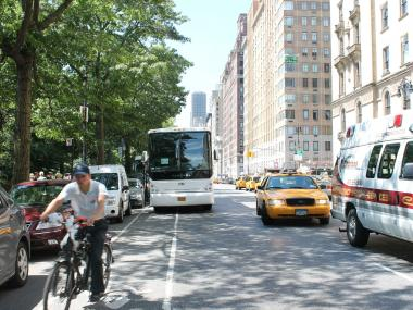 A double parked tour bus hems the flow of traffic along Central Park West and interferes with the bike lane.