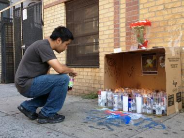 A passerby stops to look at a makeshift memorial in front of the Bronx home of Juan Acosta at 61 East 182nd Street, July 10, 2012.