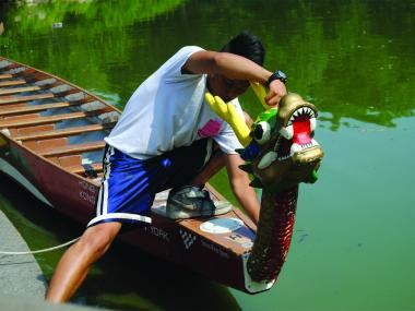 A young man affixes the dragon's head to the prow of a boat, July 12, 2012.