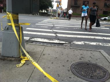 Women cross the intersection at E. 170th Street and Grand Concourse on July 14, were two men were hit and one killed earlier that day.