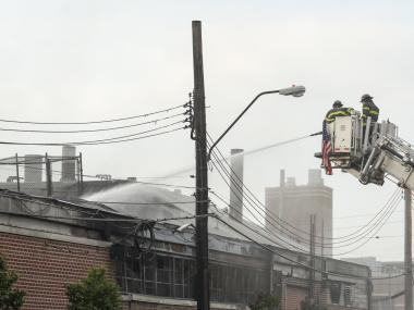 Firefighters operating at the scene of the four-alarm fire on Monday July 30, 2012.