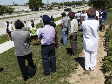Bystanders looks on as SWAT officers surround the Sikh Temple of Wisconsin where at least one gunman stormed a mass and opened fire August, 5, 2012 Oak Creek, Wisconsin. At least six people were killed when a shooter, who was shot dead by a police officer, opened fire on congregants in the Milwaukee suburb.