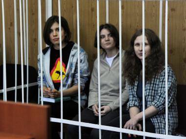 Members of the all-girl punk band 'Pussy Riot' Nadezhda Tolokonnikova (L), Maria Alyokhina (R) and Yekaterina Samutsevich (C), sit behind bars during a court hearing in Moscow on July 23, 2012.