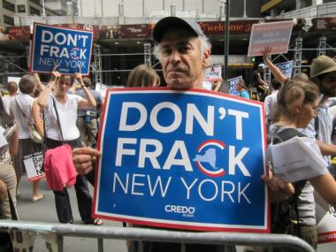"A protester holds up a sign bearing the slogan ""Don't Frack NY"" during the protest on Seventh Avenue and West 53rd Street on Wednesday, Aug. 22, 2012."