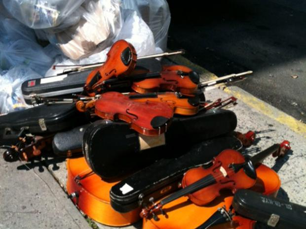 Cellos and violins sit on the street next to a pile of garbage outside Hunter College High School on 95th Street and Park Avenue, Aug. 30, 2012.