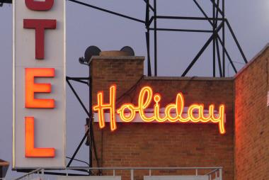 A man and a woman were shot outside the Holiday Motel on October 13, 2012. A photo of the Holiday Motel sign at dusk, December 2008.