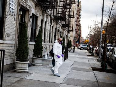 Investigator in a hazmat suit leaves an apartment where a man was found dead December 22, 2012, after a smell emerged over a week's time, neighbors said.