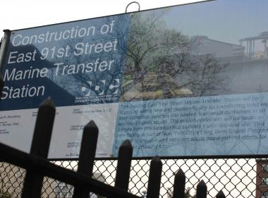 "This construction sign reads: ""The existing East 91st Marine Transfer Station will be replaced with a new and modern facility for transferring solid waste from collection vehicles into sealed leak proof containers in an enclosed indoor space.  The sealed containers will be taken on barges from this location to a sanitary waste disposal site.  This new facility is part of the New York City Long Term Export Program orientated to improve and enhance waste management efforts for a clean and healthy City."""