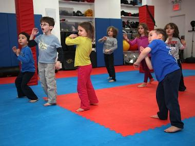 "Children enrolled at the IKM studio learn basic Krav Maga defense tactics, standing in ""fight stance."""