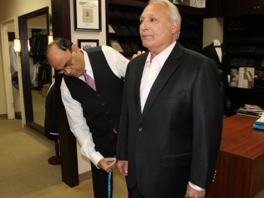 Long-time tailor Mohan Ramchandani perform a fitting inside his office across the street from Grand Central. Ramchandani pleaded guilty to evading nearly $2 million in taxes over at least 10 years on Tuesday, March 5, 2013.