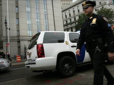 A New York City police officer walks past a Homeland Security vehicle outside of U.S. District Court in Manhattan during a court appearance for three men brought from England to New York to face terrorism charges on Oct. 9, 2012.
