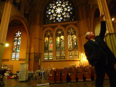 Pastor Daniel Meeter points out stained glass windows in the sanctuary at Old First Reformed Church, which has been housing the Hurricane Sandy Relief Kitchen since November 2012.