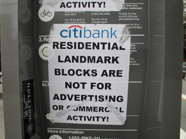 "Some locals are not happy about Citi Bike Shares in the neighborhood, posting signs that read ""Residential landmark blocks are not for advertising or commercial activity."""