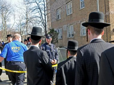Members of the community gather outside a Williamsbugh apartment building after the vandalism of another mezuzah at 130 Clymer Street on Apr. 9, 2013.