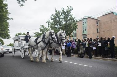 D'aja Robinson's casket was placed inside a horse carriage following the funeral.