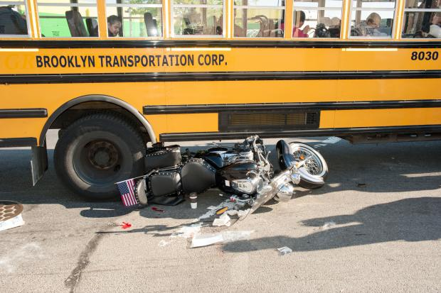 A school bus from Brooklyn Transportation Corp. collided with a motorcycle as they both turned onto 48th Street in Brooklyn while traveling eastbound on Second Avenue. The motorcycle became wedged underneath the right side of the bus at the rear tires. The motorcyclist was transported to a Lutheran Hospital.
