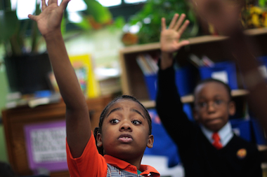 Third-grade students Tyler Smalls, left, and Sekou Cisse raise their hands in reading comprehension class at Harlem Success Academy in March 2009.