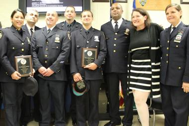 "Presentation of the ""Cop of the Month"" Award at the 112th Precinct. Left to right: Officer Michelle Feldman, Capt. Thomas Conforti, Lt. Brian Goldberg, Officers Ronald Mazzaglia and Thomas Daniele, Police Department Chief Philip Banks III, Heidi Chain, President of the 112th Precinct community council, and Chief Diana Pizzuti."