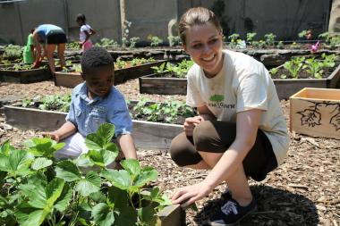 Kelly Gillen, 23, program coordinator for Harlem Grown, picks strawberries with a student from P.S. 175. June 8, 2013