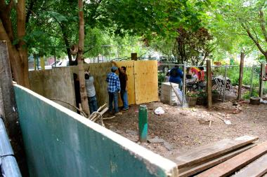 Workers put up a plywood fence in the Children's Magical Garden earlier this year, blocking off the portion owned by developer Serge Hoyda.