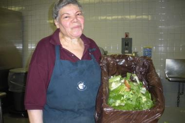A school cafeteria worker at the Upper West Side's O'Shea campus holding a bin with food scraps for compost.