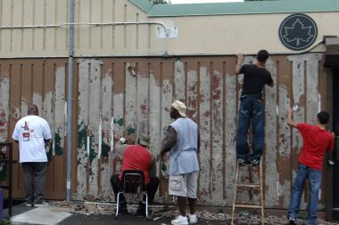 Volunteers work on the outside of Herbert Von King Park's cultural arts center.
