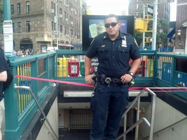 A police officer stands outside the Christopher Street station July 15, 2013, after a man died in the roadbed, the MTA said.