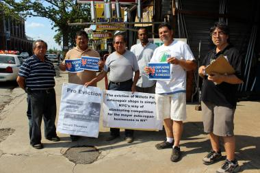 Workers from Willets Point and the Sunrise Corporation, including Marco Neira in the white t-shirt, protest the redevlopment of the area.