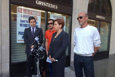 Victims in the orange and white stand with City Council Speaker Christine Quinn and State Senator Brad Hoylman at a press conference on Thursday.