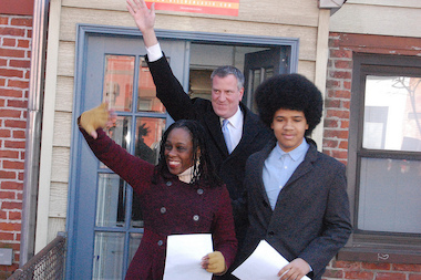 Chirlane McCray (L), Bill de Blasio (C) and Dante de Blasio (R) wave to supporters.