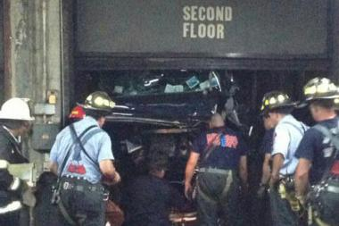 A worker survived after a car he was driving plummeted down an elevator shaft from the fifth floor of a garage at 305 East 80th Street, Sept. 5, 2013.