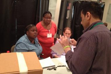 A poll worker explained paper ballots to other workers at a Midtown polling place with a broken machine.