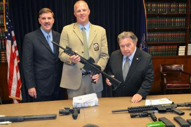 Queens District Attorney Richard A. Brown (far right) and (l-r) NYPD Inspector Michael E. Bryan, Commanding Officer, Queens Narcotics Division, and Detective Andrew Lenski display weapons recovered after busting a family that allegedly ran a Queens-based gambling ring, Sept. 24, 2013.