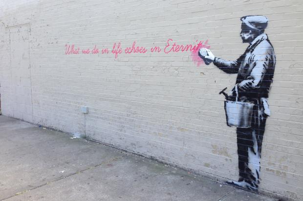 The famed street artist etched a quote along a brick building in Woodside on Monday.