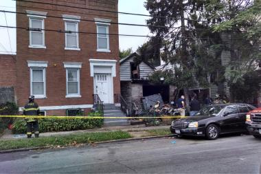 A woman died when an Elmhurst home was engulfed in flames early Monday, sources said.