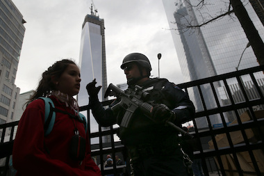 "A member of the NYPD's ""Hercules Team"" moves pedestrians along near the One World Trade tower on April 16, 2013 in New York City."