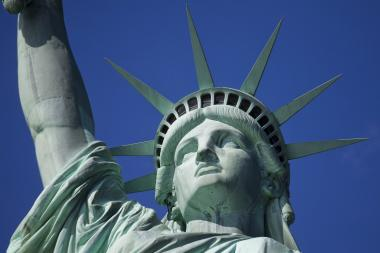 A man dressed as the Statue of Liberty was arrested after harassing a tourist who took a photo with him, police said.