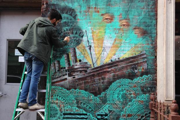 "Beau  Stanton installed the Little Italy mural ""Cursum Perficio."""