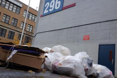 Trash left on the sidewalk outside I.S. 296 is drawing an uncontrollable amount of rats, locals said.