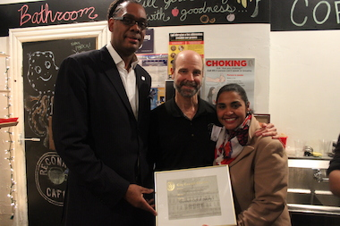 Robert Cornegy and then-Councilwoman Diana Reyna present a City Council citation to Fr. Jim O'Shea, co-owner of Reconnect Cafe on Dec. 6, 2013. Cornegy will replace Reyna as the Council's small business committee chair.
