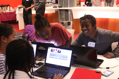 Lake Sheffield, right, jokes with others at a Black Girls Code event in December 2013. The organization is one of several in the city focused on improving girls' science and math skills.