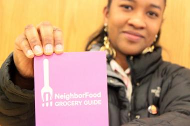 Tanya Castro, a Two Bridges resident, holds up the new food and shopping guide from the Two Bridges Neighborhood Council.