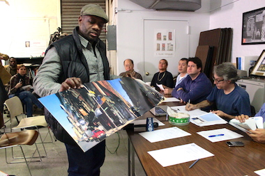 "LeRoy McCarthy shows Community Board 3 members the full ""Paul's Boutique"" album cover."