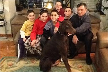 Hearing-impaired Roman Erikhman, right, pets his former service dog, Big Honey John, while seated at home with his five grandsons.
