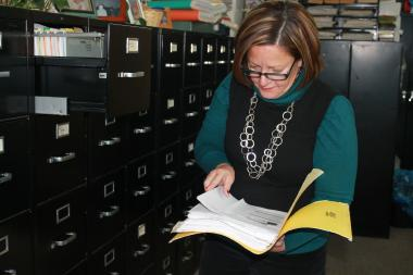 Elvira Castro, manager of Su Casa Travel Bureau, sifting through files.