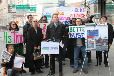 John Raskin of the Riders Alliance urges the city to allocate funding for bus countdown clocks. Next to him, Manhattan Borough President Gale Brewer shows her support.