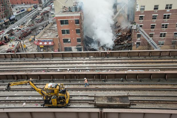 MTA crews worked to clear debris from elevated Metro-North tracks after an explosion along Park Avenue Wednesday.