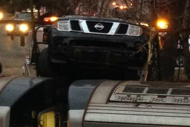 An SUV crashed through a fence and landed on a Q train in Flatbush Wednesday, the MTA said.