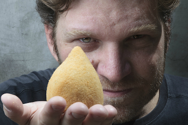 Carlos Bertolazzi holds up a coxinha. He will serve his take on the Brazilian street food at Smorgasburg on Saturday.